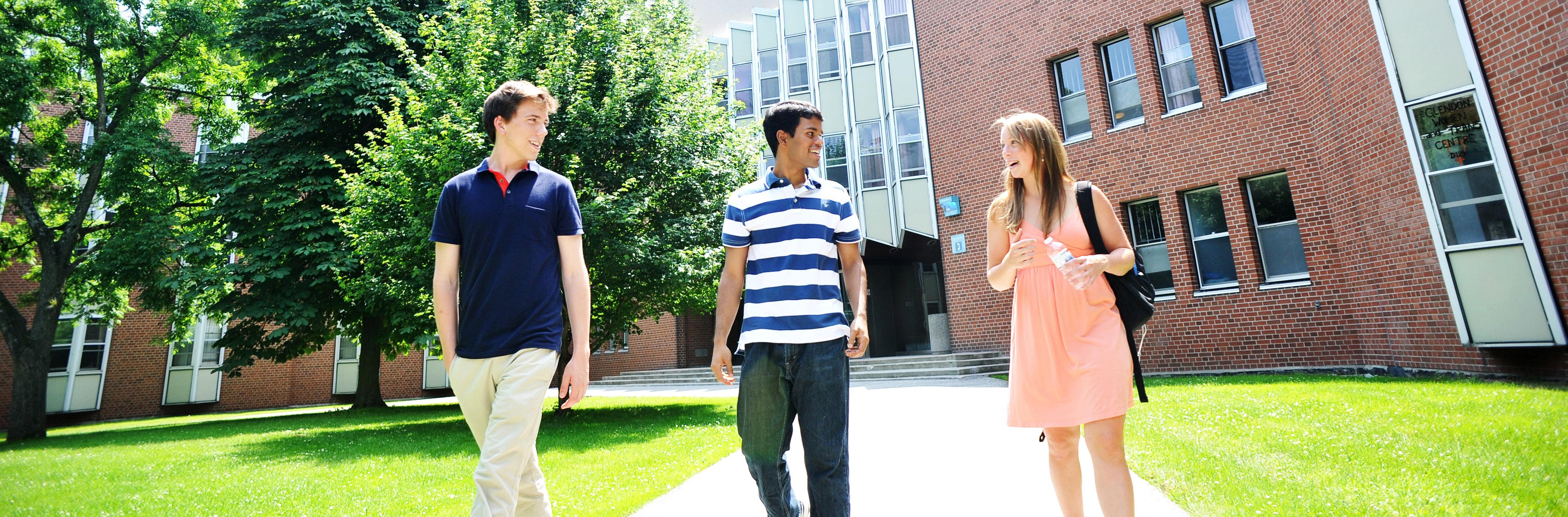 Trois etudiants marchant sur le campus