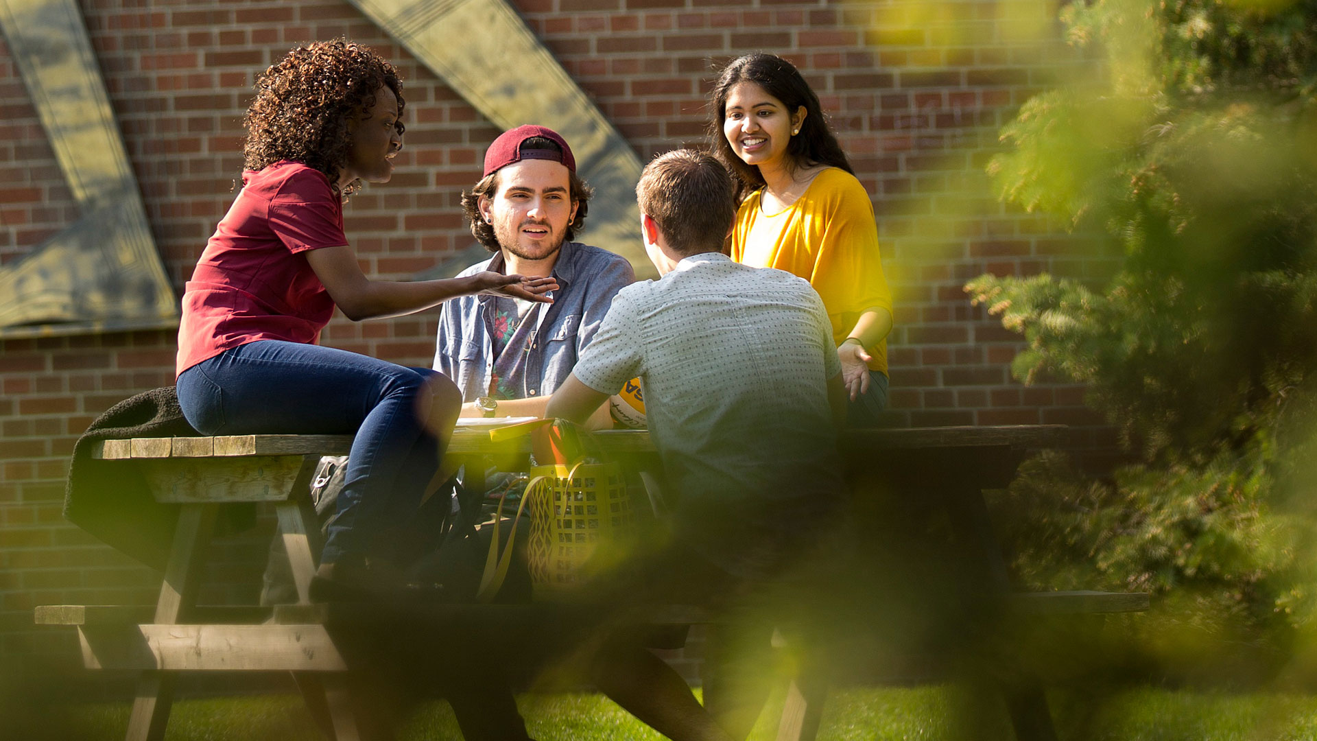Students talking at a table in front of the Whole Person