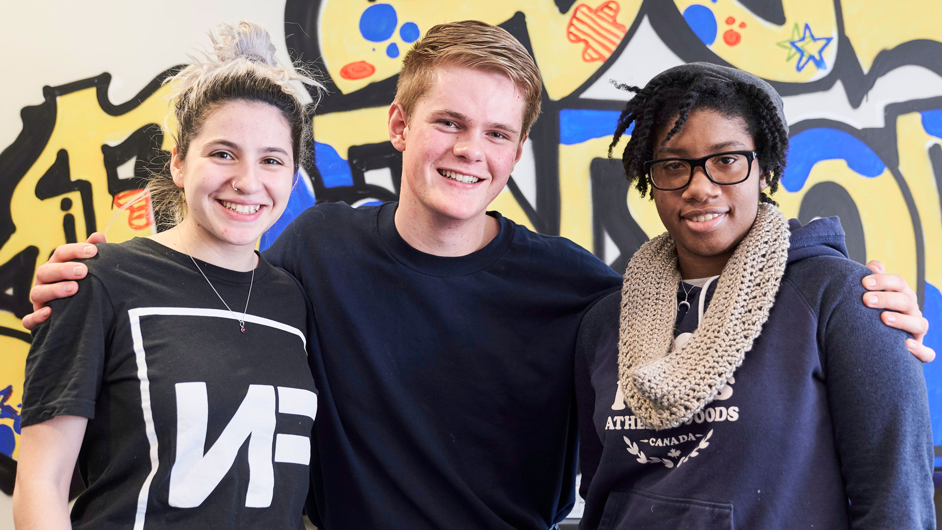 Three students in front of a mural